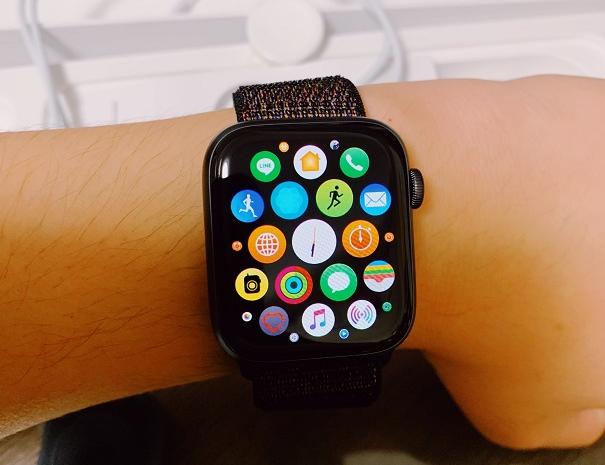 アップルウォッチを腕に巻いて時刻を確認する写真