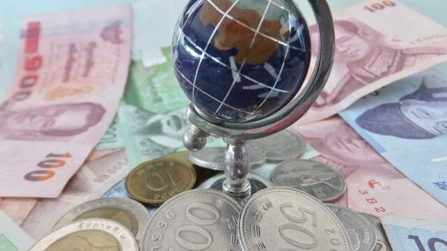 世界の通貨の上に地球儀がある